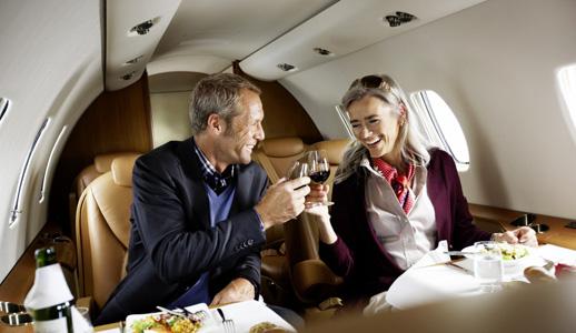 zwei-gescha%c2%a4ftsreisende-sitzen-im-lufthansa-private-jet-xls-sie-essen-und-trinken-wein-two-business-travellers-are-sitting-in-the-lufthansa-private-jet-xls-they-are-eating-and-drinking