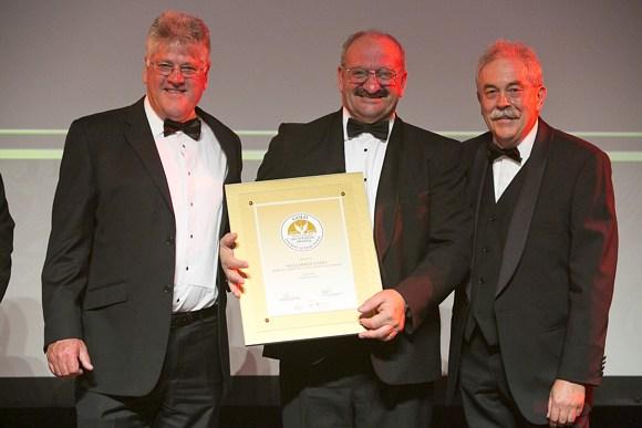 Chairman Kevin Broom und Australian Golden Outback CEO Jac Eebeek überreichen Alf Caputo den Tourismus-Award 2012 in Gold