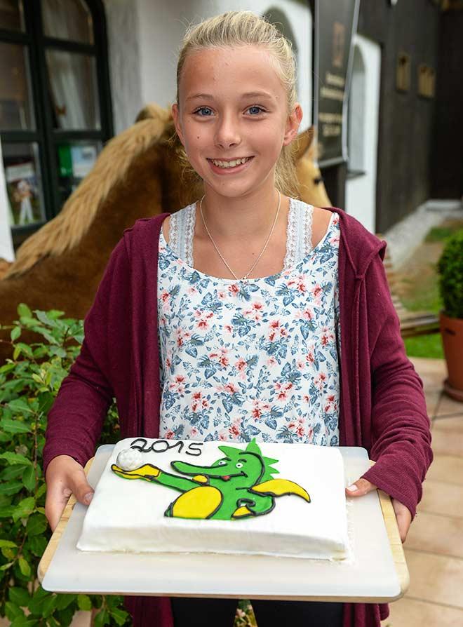 Antonia bringt eine Torte mit dem Tabaluga-Drachen