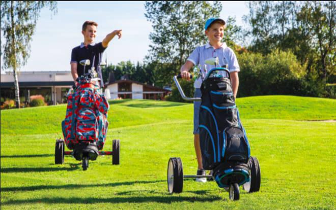 Beide Teenager fahren einen Junior Caddys Titan 3-rädrig mit Golfbag Camouflage (li.) und Golfbag Spirit (re.).