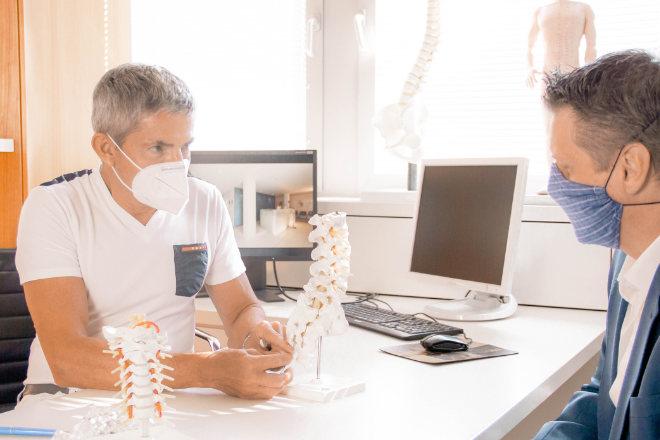 Rückenschmerzen welcher Arzt - Dr. Reinhard Schneiderhan erklärt einem Patienten den Eingriff (ⓒMVZ-München-Taufkirchen