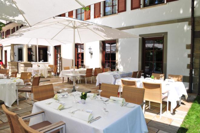 Die Hotel-Terrasse wird für Frühstück und Dinner genutzt. Das Gourmet-Restaurant versteckt sich hinter den rechten bodentiefen Fenstern.